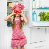 Ντομάτες λίγων κοριτσιών μαγείρων holdin όπως τα μάτια Στοκ Εικόνες