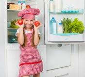 Ντομάτες λίγων κοριτσιών μαγείρων holdin όπως τα μάτια Στοκ Φωτογραφία