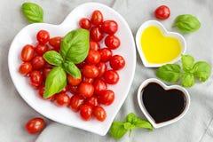 Ντομάτες, βασιλικός, έλαιο και ξίδι πρόχειρων φαγητών για να κάνει μια υγιή σαλάτα Στοκ Φωτογραφία