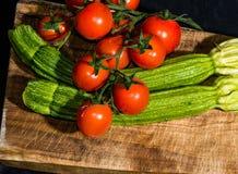 Ντομάτες και κολοκύθια στον τέμνοντα πίνακα Στοκ φωτογραφίες με δικαίωμα ελεύθερης χρήσης