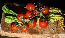 Ντομάτες και κολοκύθια στον τέμνοντα πίνακα Στοκ Φωτογραφίες