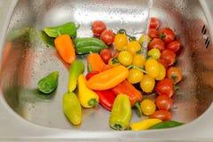 Ντομάτες και πιπέρια κερασιών πλύσης σε έναν νεροχύτη μετάλλων στοκ εικόνες
