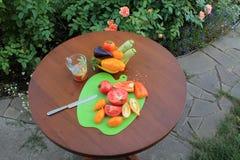 Ντομάτες και πιπέρια που τεμαχίζονται στον τέμνοντες πίνακα και το ποτήρι του χυμού Στοκ φωτογραφία με δικαίωμα ελεύθερης χρήσης