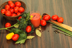 Ντομάτες και ποτήρι του χυμού ντοματών στον πίνακα Στοκ Εικόνες