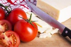 Ντομάτες και τυρί με το μαχαίρι στον τεμαχίζοντας πίνακα Στοκ εικόνα με δικαίωμα ελεύθερης χρήσης