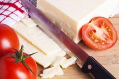 Ντομάτες και τυρί με το μαχαίρι στον τεμαχίζοντας πίνακα Στοκ Εικόνες