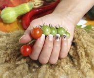 Ντομάτες κερασιών και ένα χέρι γυναικών Στοκ φωτογραφίες με δικαίωμα ελεύθερης χρήσης
