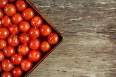 Ντομάτες κερασιών με το ελαιόλαδο αλατιού, πιπεριών και στον εκλεκτής ποιότητας δίσκο ψησίματος στον ξύλινο πίνακα Στοκ εικόνες με δικαίωμα ελεύθερης χρήσης