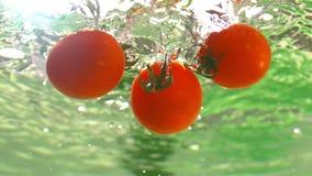 Ντομάτες κερασιών που εμπίπτουν στο νερό με τις φυσαλίδες σε σε αργή κίνηση υποβρύχιο βλασταημένο Tabletop 1500 fps φιλμ μικρού μήκους
