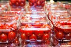 Ντομάτες κερασιών που συσκευάζονται στα πλαστικά εμπορευματοκιβώτια Στοκ εικόνα με δικαίωμα ελεύθερης χρήσης