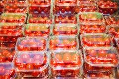 Ντομάτες κερασιών που συσκευάζονται στα πλαστικά εμπορευματοκιβώτια Στοκ εικόνες με δικαίωμα ελεύθερης χρήσης