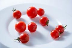 Ντομάτες κερασιών στο άσπρο πιάτο στοκ φωτογραφία