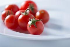 Ντομάτες κερασιών στο άσπρο πιάτο στοκ εικόνα