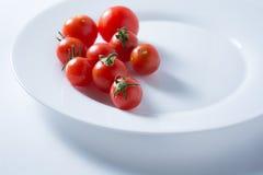 Ντομάτες κερασιών στο άσπρο πιάτο στοκ εικόνες