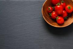 Ντομάτες κερασιών στο ξύλινο κύπελλο στη μαύρη επιφάνεια πετρών Τοπ άποψη με το διάστημα αντιγράφων Στοκ φωτογραφίες με δικαίωμα ελεύθερης χρήσης