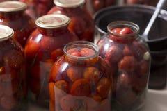 Ντομάτες που προετοιμάζονται για την κονσερβοποίηση των σπιτιών στα βάζα γυαλιού στοκ εικόνα