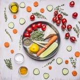 Ντομάτες σε έναν κλάδο των αγγουριών λεμονιών καρυκευμάτων χορταριών θυμαριού και των καρότων ντοματών σε ένα τηγάνι με τα λαχανι Στοκ Εικόνες