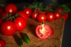 Ντομάτες σε ξύλινο με τα πράσινα pappers στοκ φωτογραφίες