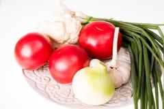 Ντομάτες, σκόρδο, κρεμμύδι και φρέσκο κρεμμύδι στο πιάτο που απομονώνεται Στοκ Φωτογραφία