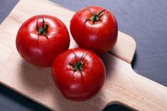 Ντομάτες στον τέμνοντα πίνακα Στοκ φωτογραφίες με δικαίωμα ελεύθερης χρήσης