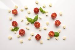 Ντομάτες, τυρί, βασιλικός σε ένα άσπρο υπόβαθρο ντομάτα σαλαμιού πιτσών paprica συστατικών τυριών Στοκ Φωτογραφία