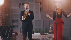 Ντουέτο της Jazz στη σκηνή Ο ελκυστικός αοιδός Saxophonist τραγουδά και χτυπά τα δάχτυλα φιλμ μικρού μήκους