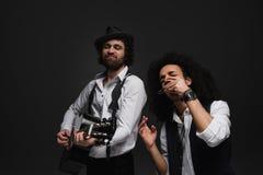 ντουέτο των εκφραστικών μουσικών που παίζουν την ακουστικές κιθάρα και τη φυσαρμόνικα στοκ φωτογραφίες
