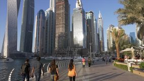 Ντουμπάι, Ε.Α.Ε. - 13 Ιανουαρίου 2018: Τουρίστες που περπατούν στη μαρίνα του Ντουμπάι με τους όμορφους ουρανοξύστες στο υπόβαθρο απόθεμα βίντεο