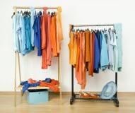 Ντουλάπα με τα συμπληρωματικά πορτοκαλιά και μπλε ενδύματα χρωμάτων στις κρεμάστρες στοκ εικόνα με δικαίωμα ελεύθερης χρήσης