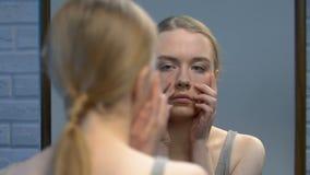 Ντροπαλή νέα κυρία που κοιτάζει στον καθρέφτη και το κλείνοντας πρόσωπο με τα χέρια, ατέλειες δερμάτων φιλμ μικρού μήκους