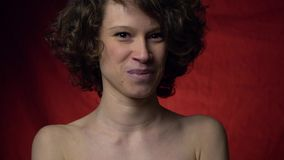 Ντροπαλό χαριτωμένο χαμόγελο brunette που στέκεται στο κόκκινο υπόβαθρο απόθεμα βίντεο