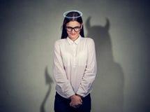 Ντροπαλή ήρεμη γυναίκα αγγέλου με το χαρακτήρα διαβόλων στοκ εικόνα