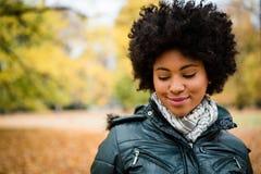 Ντροπαλή νέα χαμογελώντας γυναίκα στο πάρκο φθινοπώρου Στοκ Εικόνες