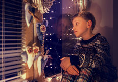 Ντυμένο μικρό παιδί πουλόβερ Χριστουγέννων που κοιτάζει μέσω του παραθύρου Στοκ φωτογραφία με δικαίωμα ελεύθερης χρήσης