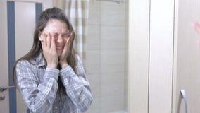 Νυσταλέα γυναίκα με την απόλυση στο λουτρό που εξετάζει την αντανάκλασή της στον καθρέφτη φιλμ μικρού μήκους