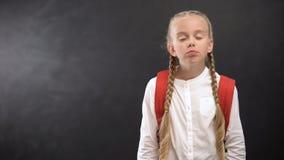 Νυσταλέα μαθήτρια που χασμουριέται στη κάμερα ενάντια στον πίνακα, κούραση μετά από τα μαθήματα απόθεμα βίντεο