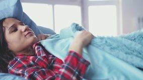 Νυσταλέα νέα γυναίκα brunette που φορά τις πυτζάμες που βρίσκονται στο κρεβάτι στο δωμάτιό της σε σε αργή κίνηση Κορίτσι coveres  απόθεμα βίντεο