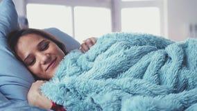 Νυσταλέα νέα όμορφη γυναίκα που βρίσκεται στο κρεβάτι που ξυπνά επάνω να τεντώσει και που χαμογελά ob το θολωμένο παράθυρο στο υπ απόθεμα βίντεο
