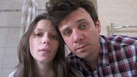 Νυσταλέοι άνδρας και γυναίκα ζευγών στο λουτρό με την απόλυση που προσπαθεί ξυπνήστε απόθεμα βίντεο