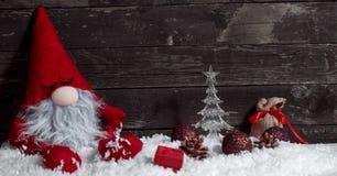 Νυσταλέος νάνος Χριστουγέννων στο χιόνι με τα Χριστούγεννα διακοσμητικά Στοκ Εικόνες
