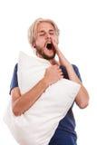 Νυσταλέος νεαρός άνδρας που κρατά το άσπρο μαξιλάρι Στοκ εικόνα με δικαίωμα ελεύθερης χρήσης