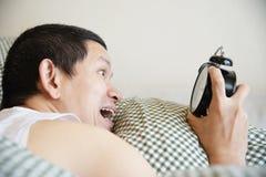Νυσταλέο άτομο που κρατά το ξυπνητήρι το πρωί με αργά ξυπνήστε στοκ εικόνες
