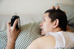 Νυσταλέο άτομο που κρατά το ξυπνητήρι το πρωί με αργά ξυπνήστε στοκ εικόνες με δικαίωμα ελεύθερης χρήσης