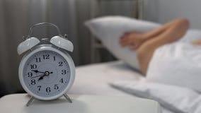 Νυσταλέο θηλυκό που ενοχλείται από τα χτυπώντας κλείνοντας αυτιά ξυπνητηριών με το μαξιλάρι, αεριωθούμενη καθυστέρηση στοκ φωτογραφίες με δικαίωμα ελεύθερης χρήσης
