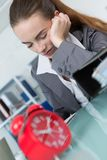 Νυσταλέο κουρασμένο κορίτσι που τρυπιέται με την εργασία στην αρχή Στοκ Φωτογραφίες