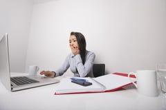 Νυσταλέα επιχειρηματίας που εργάζεται στο lap-top στο γραφείο γραφείων Στοκ Εικόνες