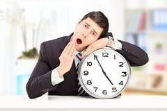 Νυσταλέος νέος επιχειρηματίας που κλίνει το κεφάλι του σε ένα μεγάλο ρολόι τοίχων, ι Στοκ φωτογραφία με δικαίωμα ελεύθερης χρήσης