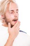 Νυσταλέος νεαρός άνδρας που κρατά το άσπρο μαξιλάρι Στοκ Εικόνες