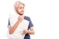 Νυσταλέος νεαρός άνδρας που κρατά το άσπρο μαξιλάρι Στοκ Φωτογραφίες
