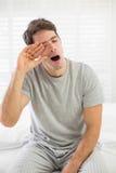 Νυσταλέο άτομο που χασμουριέται δεδομένου ότι τρίβει το μάτι του στο κρεβάτι Στοκ Εικόνα